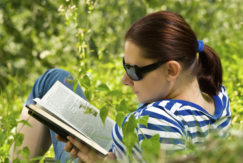 Young Woman Reading Bible In The Natural Environment